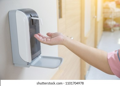 hand under the automatic alcohol dispenser. Infection and hospitably concept. save and clean in the public area.