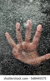 Hand underneath frozen lake pushing up from below the ice as man is drowning. Dark background and bubbles in the ice.