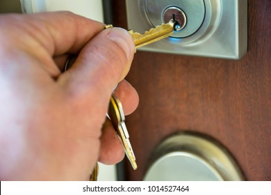 Hand unlocking pad lock of brand new modern home at the front door of wooden door with male white hand about to Turn the Key on his first Brand New Brick Home in the Suburbs