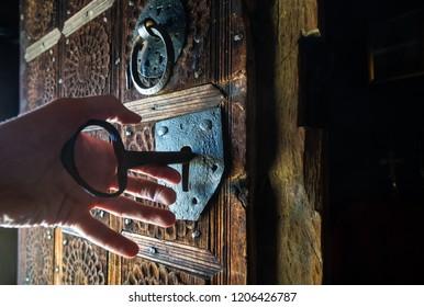 Hand unlocking rustic door of wooden church with a big key