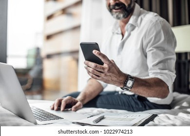 Hand of unrecognisable businessman typing on cell phone.