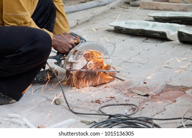 A hand of urban technician working a cutter steel machine on the red brick for constuction