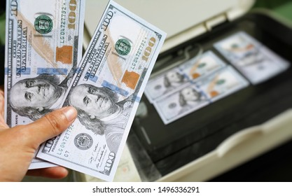 Hand with us dollars cash, blurred printer and printed US dollars, counterfeit banknote, currency counterfeiting. Counterfeiters, printing press, inflation