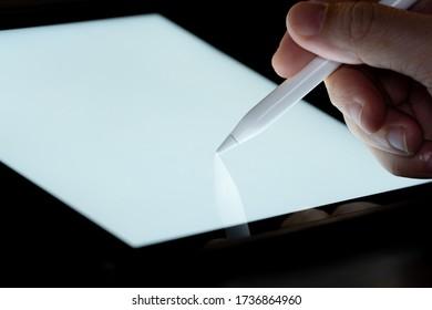 ペンのペンのスタイラスで触れ、タブレット画面に明るくモックアップしてドローします。 携帯電話の技術と将来の外観のコンセプト。
