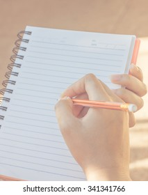 hand use pencil writing on notebook