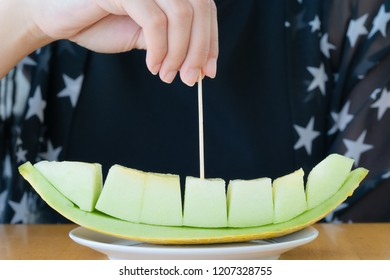 hand use wooden toothpick pick piece of green melon