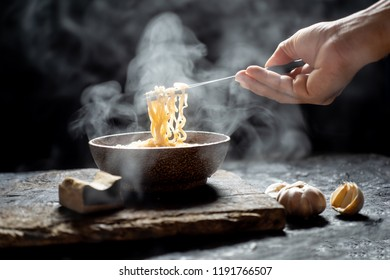 Hand uses chopsticks to tasty noodles with steam and smoke in bowl on wooden background, selective focus. Asian meal on a table, junk food concept