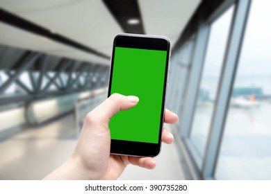 Hand uses a phone with a touch screen and place a copy in green. Airport terminal in fuzzy depth of field.