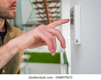 Hand using an automation screen in a modern space.