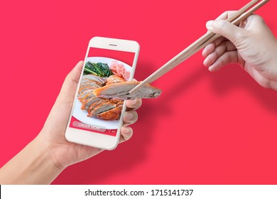 hand using chopsticks to clamp the roasted duck from application to made order food online via mobile smartphone, isolated on red background. online food order and delivery service advertise concept.