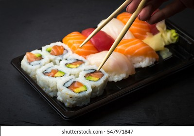 Hand using chopsticks pick Sushi and Sashimi rolls on a black stone slatter. Fresh made Sushi set with salmon, prawns, wasabi and ginger. Traditional Japanese cuisine.