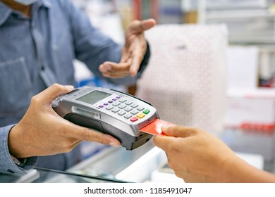 hand using credit card swiping machine to pay. Hand with creditcard swipe through terminal for payment in cafeteria. Man entering credit card code in swipe machine.