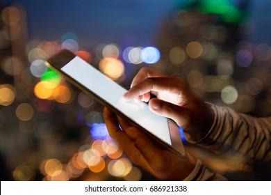 hand using digital tablet on night beauty light bokeh in city