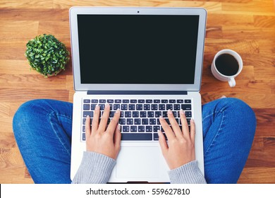 hand using laptop on wooden background