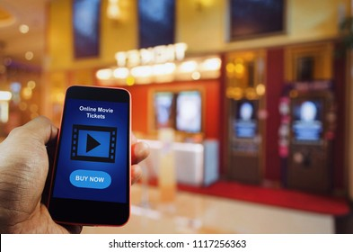 hand using mobile smart phone to buy cinema tickets with blurred image of ticket sales counter at movie theater with graphic icon diagram, reserved seating, online booking and payment concept