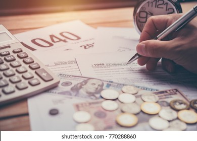 Hand using pen writing Tax forms 1040 ,calculator and money. Tax time concept.