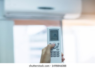 hand using remote controller for adjust Air conditioner inside the room of office or house