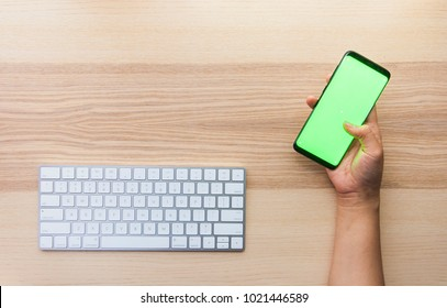 Hand using the smart phone with chroma screen on desk with copy space