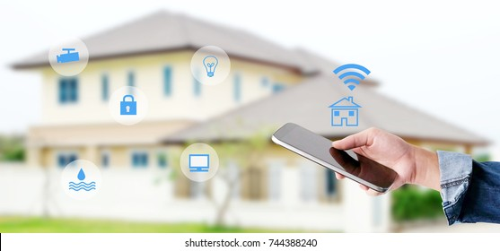 Hand using smart phone as smart home control application over blurred house background, banner, smart home concept