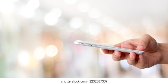 Hand using smart phone over blur bokeh light background, business and technology, internet of things concept