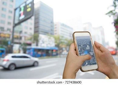 Hand using smart phone searching location on satellite navigation application and network connection over traffic transportation in city, internet of things, satellite navigation system app concept