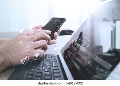 hand using smart phone,mobile payments online shopping,omni channel,digital tablet docking keyboard computer in modern office on wooden desk,virtual interface icons screen