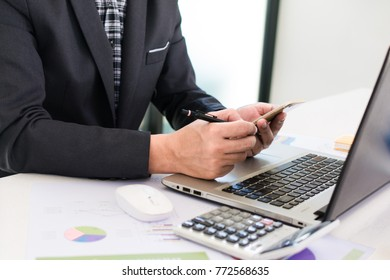 Hand using smart phone,mobile payments online shopping, Business man working in wooden desk with laptop and telephone at work space.