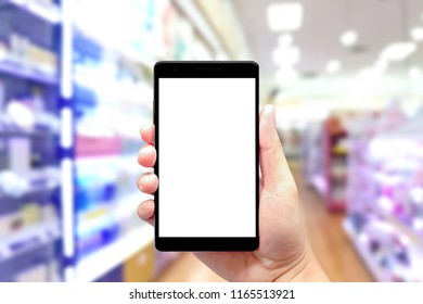 Hand using smartphone with blank screen on abstract blurred background of cosmetic shop, cosmetic shop background