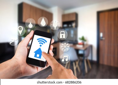 Hand using smartphone by app smart home on mobile for remote control everything in home by wifi network.