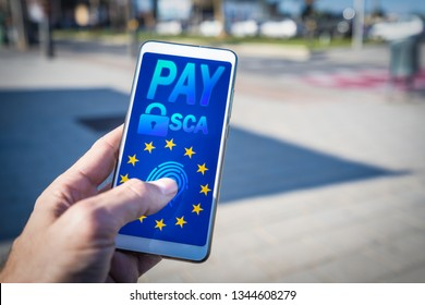 Hand using a smartphone and paying online.Strong Customer Authentication or SCA approved by the EU Revised Payment Services Directive or PSD2