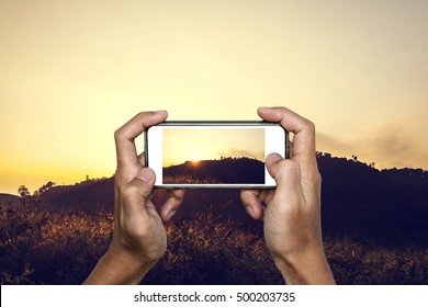 Hand using smartphone taking photo of tropical mountain landscape in sunset