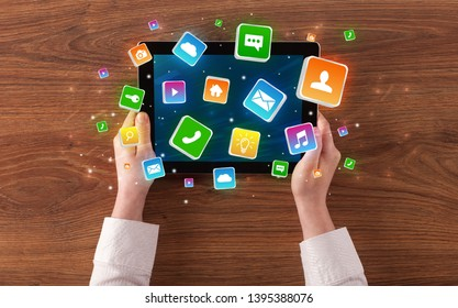 Hand using tablet with colourfull bounce application symbols and icons concept