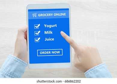 Hand using tablet with grocery shopping check list online on screen device background, grocery online, business and technology, digital marketing concept