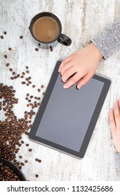 A woman's hand using a tablet next to coffeebeans on the table