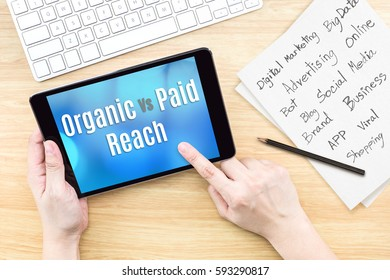 Hand using tablet with Organic vs paid reach word on screen with list of digital marketing features on paper on work table,Online business concept