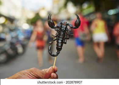 Hand of vendor with roasted scorpion. Street in Bangkok, Thailand.