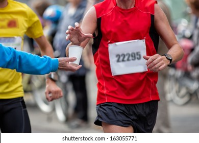 Hand of a volunteer giving a can of water at a refreshment point in a marathon race to an athlete, with the hand of the runner grabbing the water