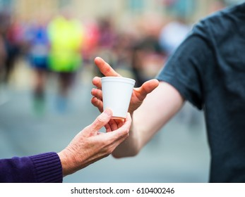 Hand of a volunteer giving a cup of water at a refreshment point in a marathon race to runners.