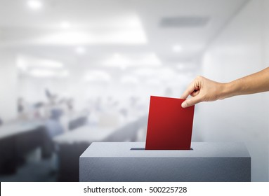 Hand of voting red ballot with box