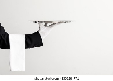 Hand of waiter with empty tray on light background