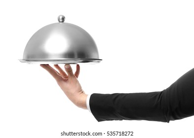 Hand of waiter holding metal tray with cover on white background