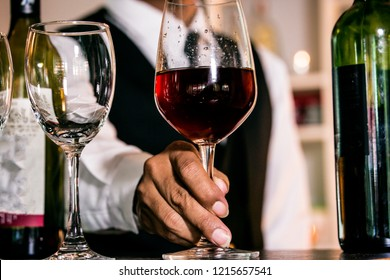 Hand Waiter pouring red wine in a glass...