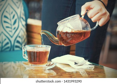 Hand of the waitress pours a cup of tea at the client's table. Close-up of the glass teapot with tea.  The waitress pours tea for the client of the hotel restaurant. Toning.