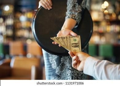 The hand of the waitress takes the tip. The waiter girl receives a tip from the client at the hotel bar. A bartender woman is happy to receive a tip at work. The concept of service.