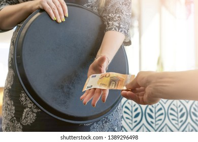 Hand of the waitress takes the tip. The waiter girl receives a tip from the client at the hotel bar. A bartender woman is happy to receive a tip at work. The concept of service. Toning.
