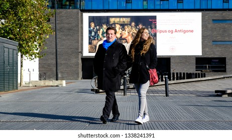 Hand in hand walking couple  with an Oedipus & Antigone show sign kissing in the backgrounds, October 8th, 2016, Copenhagen streets, Denmark.