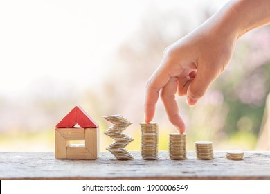 Hand walking on money coin stack with wooden house.Property investment and house mortgage financial concept,