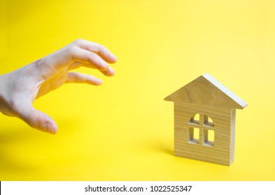 A hand wants to take the home. A high demand for real estate or seizure of property concept on a yellow background