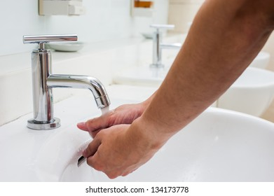 hand washing by faucet in bathroom