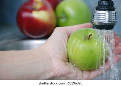 A Hand Washing a Delicious Green Granny Smith Apple in a Sink with More Apples in the Background